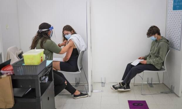 Hailey Slocombe, 21, receives a COVID-19 vaccine at an AHS site. As of Friday, 57.9 per cent of eligible Albertans (12 and up) had been fully immunized and 74.5 per cent had received at least one dose. (Submitted by Alberta Health Services - image credit)