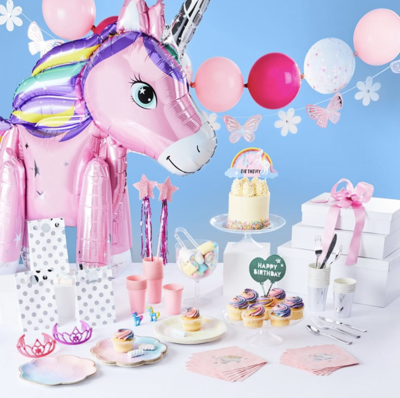 Kmart's 'magical' party themed products including a balloon unicorn, pink round balloons and pink tiaras.