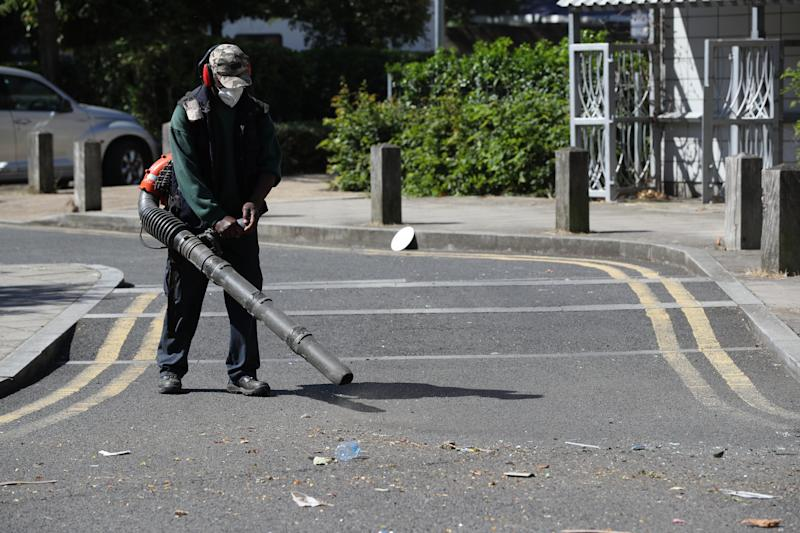 Volunteers clean up in Overton Road, Angell Town, Brixton, south London, where riots and violent confrontations with police took place overnight. Fifteen officers were injured and four people were arrested following the incident.