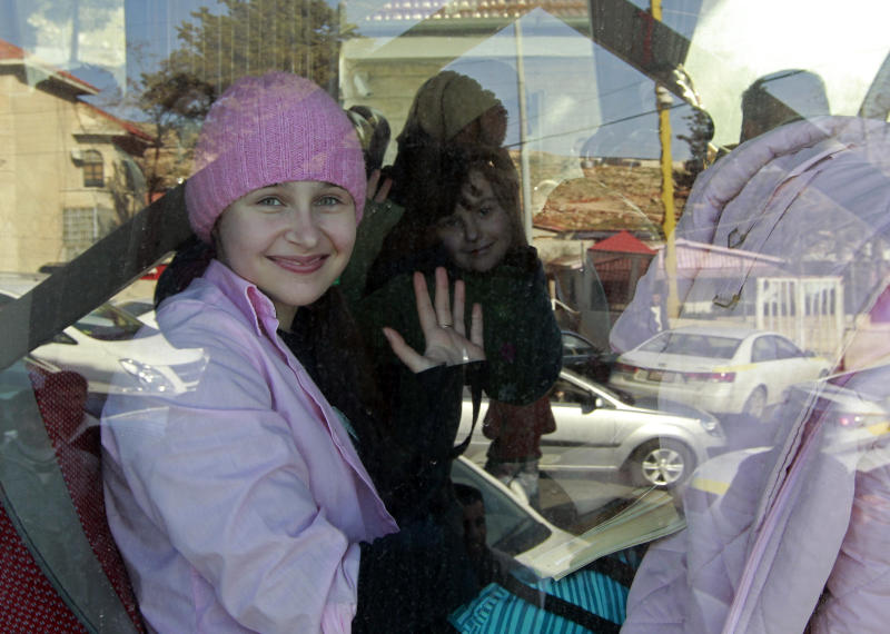 Russian citizens wave from inside a bus shortly after crossing the border from Syria into Lebanon at the Masnaa border crossing on Tuesday, Jan. 22, 2013. Some 80 Russian citizens crossed into Lebanon as Moscow began evacuating some of the tens of thousands of Russians who live in Syria. (AP Photo/Bilal Hussein)