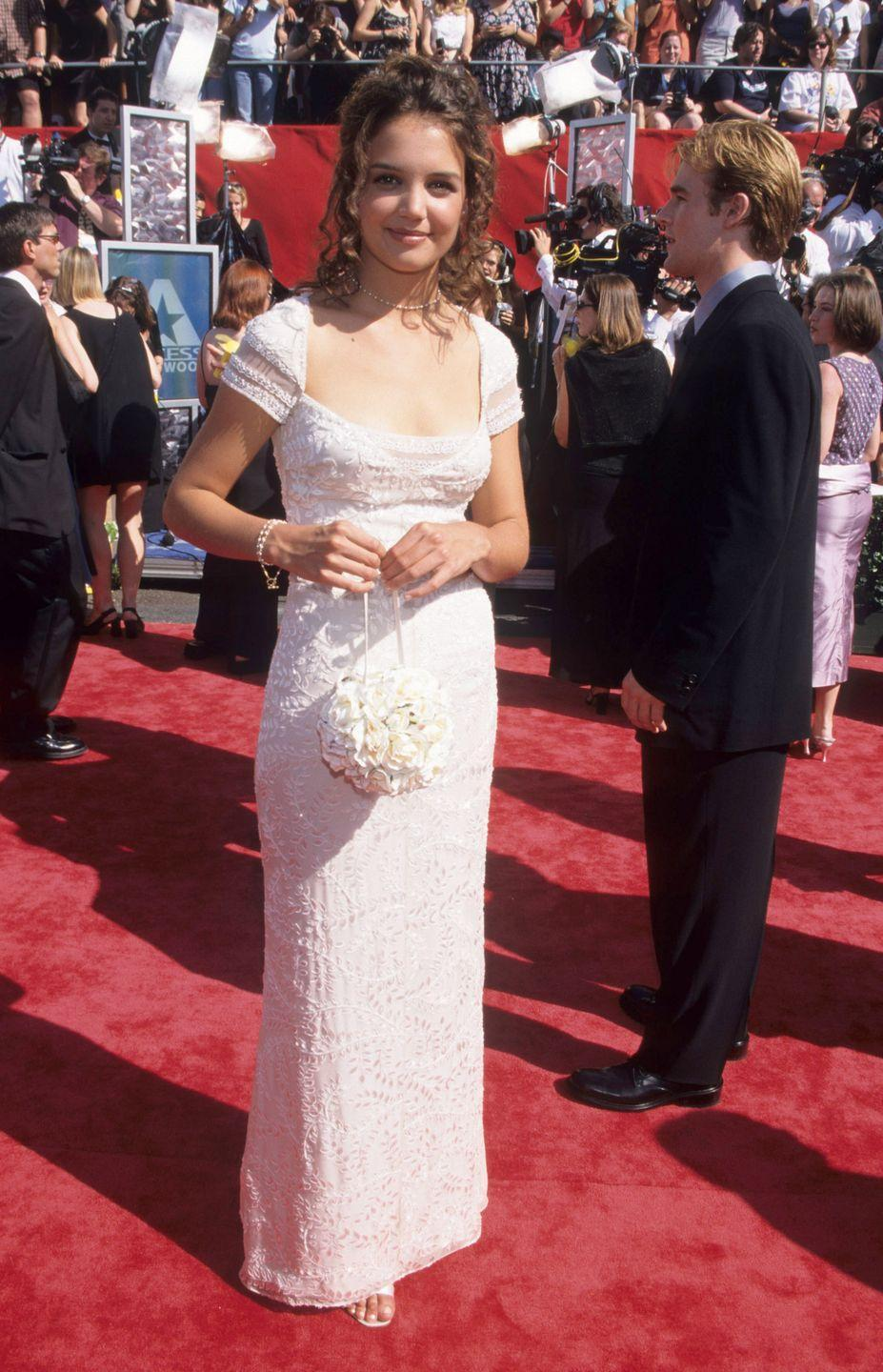 """<p>Why yes, that <em>is</em><span class=""""redactor-invisible-space""""> James Van Der Beek in the background of this picture. He escorted a cap-sleeved Holmes to the Emmy Awards in </span>1998.</p>"""