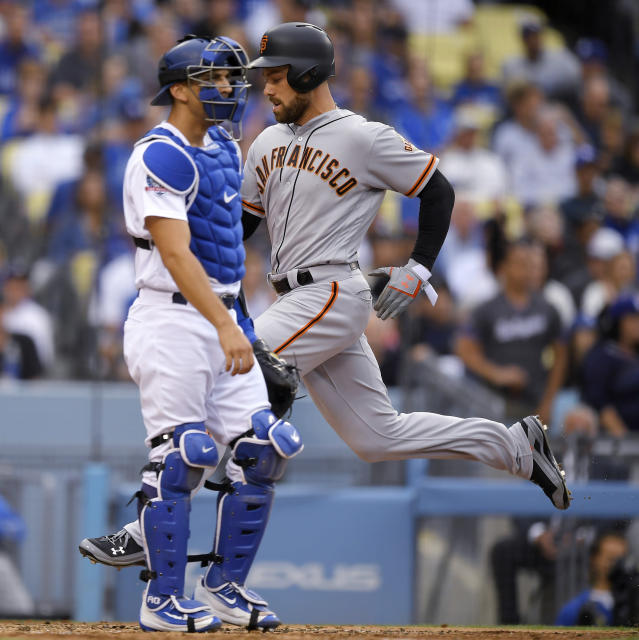 San Francisco Giants' Mac Williamson, right, scores on a sacrifice fly hit by Alen Hanson as Los Angeles Dodgers catcher Austin Barnes stands at the plate during the fifth inning of a baseball game Saturday, June 16, 2018, in Los Angeles. (AP Photo/Mark J. Terrill)