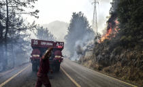 Firefighters work as the wildfires engulf an area near the seashore, forcing people to be evacuated by boats, in Bodrum, Mugla, Turkey, Sunday, Aug. 1, 2021. Wildfires in the Turkish holiday destinations of Antalya and Mugla are still raging as firefighters worked to battle the blazes for a fifth day. Authorities warned tourists and residents to keep evacuating Turunc, a town in the seaside resort of Marmaris, and navy ships waited in the sea there to see if a bigger evacuation was needed. (Ismail Coskun/IHA via AP)
