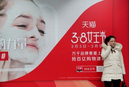 A woman stands in front of an International Women's Day advertisement by Tmall, Alibaba's e-commerce platform, at a subway station in Beijing, China March 7, 2018. Picture taken March 7, 2018. REUTERS/Jason Lee