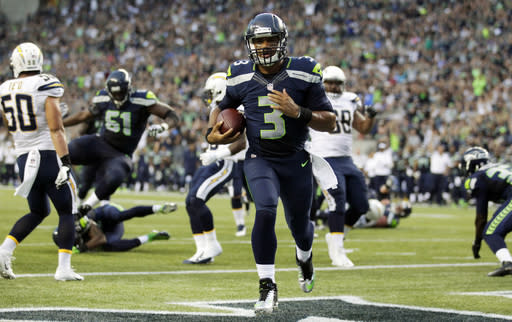 Seattle Seahawks quarterback Russell Wilson runs for a touchdown in the first half of a preseason NFL football game against the San Diego Chargers, Friday, Aug. 15, 2014, in Seattle. It was Winson's second rushing touchdown in the first half. (AP Photo/Stephen Brashear)