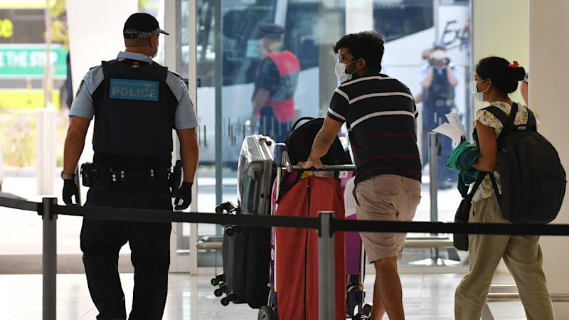 Travellers inside Adelaide Airport wear face masks as they are escorted into quarantine.