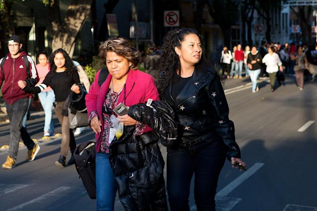 <p>People walk down the center of a street in the Roma neighborhood after an earthquake shook Mexico City, Friday, Feb. 16, 2018. (Photo: Rebecca Blackwell/AP) </p>
