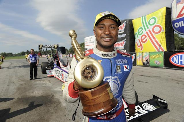 In this photo provided by the NHRA, Top Fuel driver Antron Brown raises his Wally trophy after racing to victory Sunday, July 6, 2014, in the Summit Racing Equipment NHRA Nationals at Norwalk, Ohio. Brown claimed his second consecutive victory, fifth win of the season and 46th of his career. (AP Photo/NHRA,Marc Gewertz)