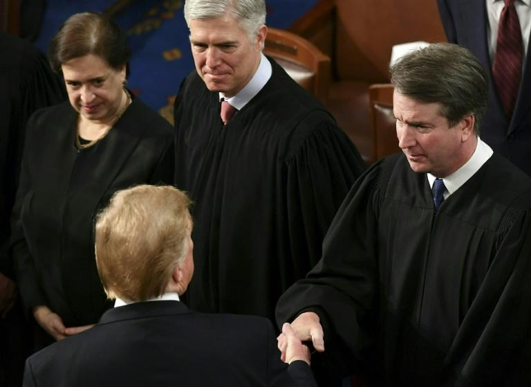 President Donald Trump (L) greets the two conservative judges he appointed to the court: Brett Kavanaugh (R) and Neil Gorsuch (center), on February 5, 2019