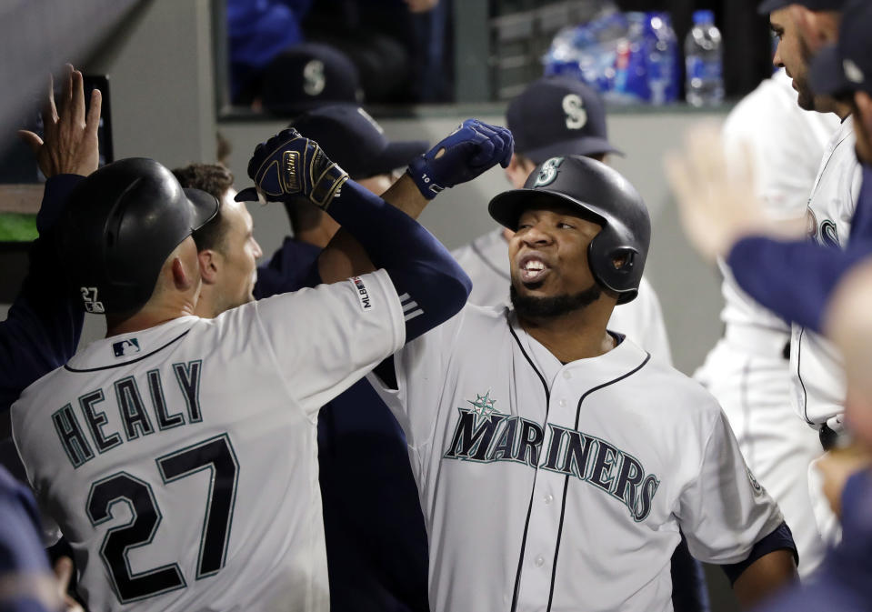 Seattle Mariners' Edwin Encarnacion, right, smiles as he is congratulatedd in the dugout after his solo home run against the Chicago Cubs during the seventh inning of a baseball game Tuesday, April 30, 2019, in Seattle. (AP Photo/Elaine Thompson)