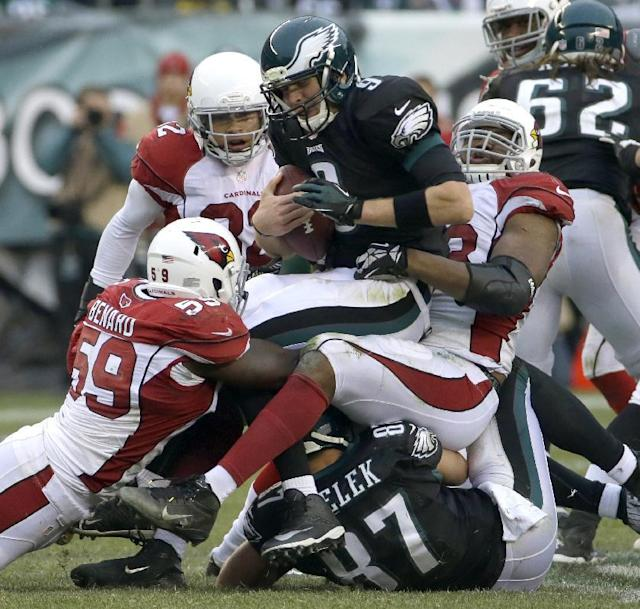 Philadelphia Eagles' Nick Foles, center, is tackled by Arizona Cardinals' Marcus Benard, left, and Daryl Washington during the second half of an NFL football game, Sunday, Dec. 1, 2013, in Philadelphia. (AP Photo/Tim Donnelly)