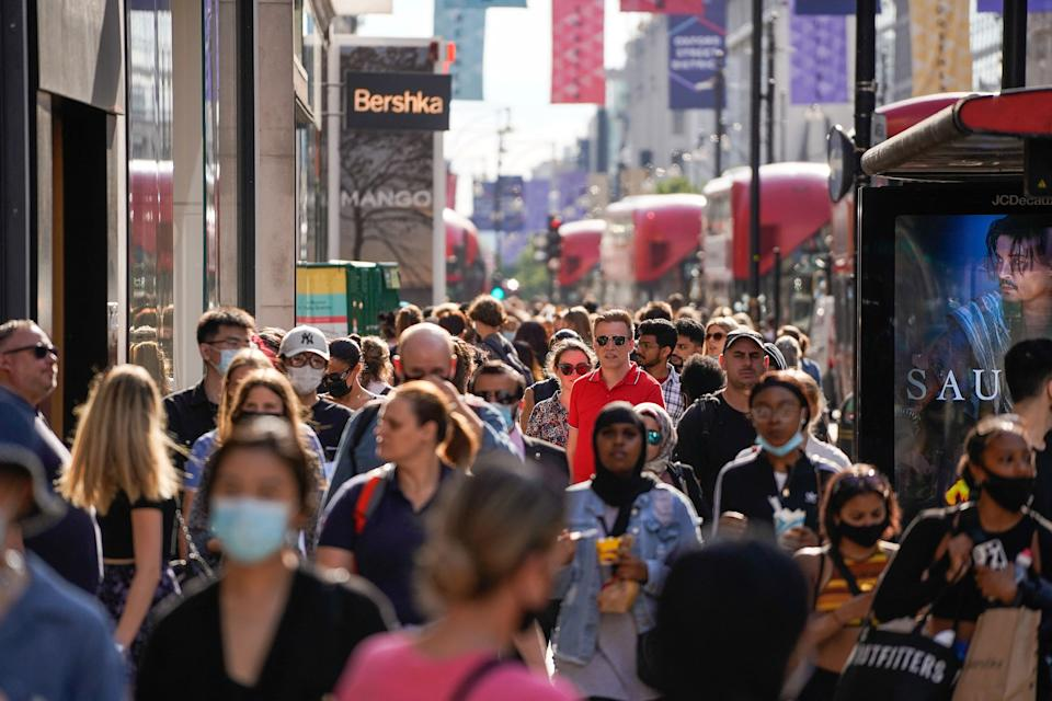 Pedestrians, some wearing face coverings due to Covid-19, walk past shops on Oxford Street in central London on June 7, 2021. - The Delta variant of the coronavirus, first discovered in India, is estimated to be 40 percent more transmissible than the Alpha variant that caused the last wave of infections in the UK, Britain's health minister said Sunday. (Photo by Niklas HALLE'N / AFP) (Photo by NIKLAS HALLE'N/AFP via Getty Images)