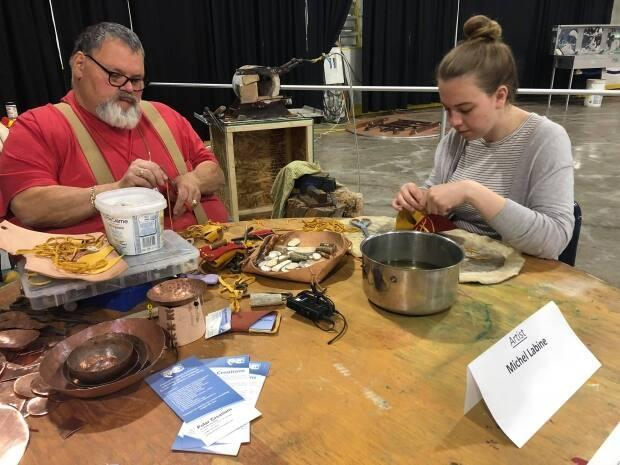 Fort Smith artist Michel Labine teaching an Inuvik resident how to make a coin purse at the Great Northern Arts Festival in 2019. (Mackenzie Scott/CBC - image credit)