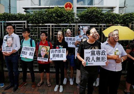 Protesters wearing masks of Chinese Nobel rights activist Liu Xiaobo stand outside China's Liaison Office in Hong Kong, China