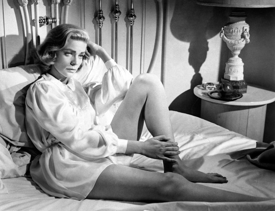 The actress wears a silk robe while sitting on the bed, sometime in the 1950s.