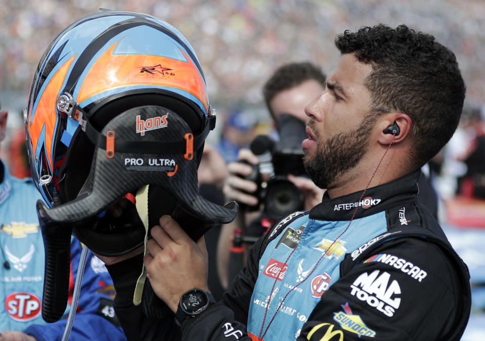 FILE- In this Feb. 17, 2019, file photo, Darrell Wallace Jr., right, prepares put on his HANS device equipped helmet before the start of the NASCAR Daytona 500 auto race at Daytona International Speedway in Daytona Beach, Fla. The lightweight head restraint co-invented by veteran sports car racer Jim Downing keeps a driver's head from snapping forward violently in a crash and has been credited with saving numerous lives in its two decades of use. (AP Photo/John Raoux, File)