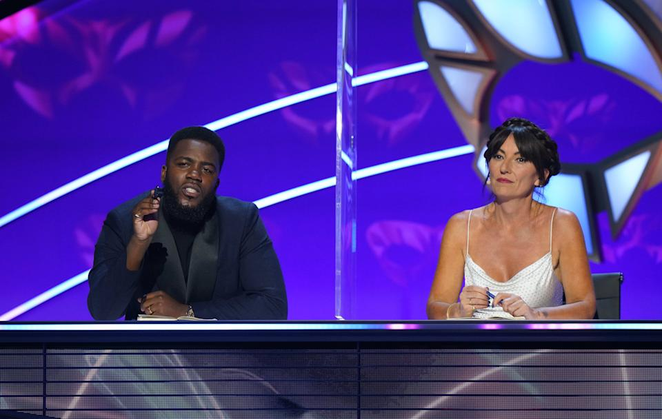 This image and the information contained herein is strictly embargoed until 00.01 Saturday 23rd January 2021  From Bandicoot TV  The Masked Singer: SR2: Ep5 on ITV  Pictured: Mo Gilligan and Davina McCall.  This photograph is (C) Bandicoot TV and can only be reproduced for editorial purposes directly in connection with the programme or event mentioned above, or ITV plc. Once made available by ITV plc Picture Desk, this photograph can be reproduced once only up until the transmission [TX] date and no reproduction fee will be charged. Any subsequent usage may incur a fee. This photograph must not be manipulated [excluding basic cropping] in a manner which alters the visual appearance of the person photographed deemed detrimental or inappropriate by ITV plc Picture Desk.  This photograph must not be syndicated to any other company, publication or website, or permanently archived, without the express written permission of ITV Picture Desk. Full Terms and conditions are available on the website www.itv.com/presscentre/itvpictures/terms  For further information please contact: james.hilder@itv.com / 0207 157 3052