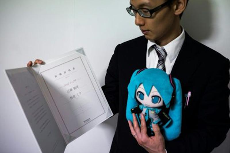 Mr Kondo tied the knot with Miku, in the form of a stuffed doll (both pictured)