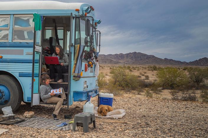 """Paula searches for jobs on her laptop while Max makes an origami card for a family member, while parked at a campsite near Quartzsite, Az., on Feb. 9. Paula says she moved into the skoolie in part in the face of economic instability caused by the pandemic. """"I'm a single mom,"""" she tells TIME. """"There's not going to be anything to catch me.""""<span class=""""copyright"""">Nina Riggio for TIME</span>"""