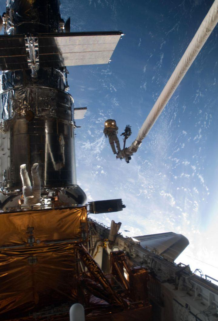 Mission Specialist John Grunsfeld is positioned on a foot restraint on the end of Atlantis' remote manipulator system and Andrew Feustel (top center), mission specialist, participate in the mission's fifth and final spacewalk.