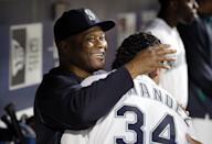 Seattle Mariners manager Lloyd McClendon, left, embraces starting pitcher Felix Hernandez after Hernandez came into the dugout after pitching the eighth inning of a baseball game against the San Francisco Giants on Wednesday, June 17, 2015, in Seattle. (AP Photo/Elaine Thompson)