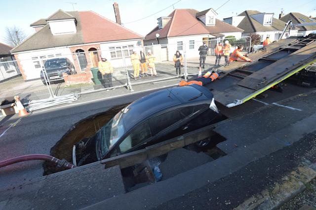 A Toyota car is removed from a sinkhole which appeared overnight in Hatch Road, Brentwood. (PA)