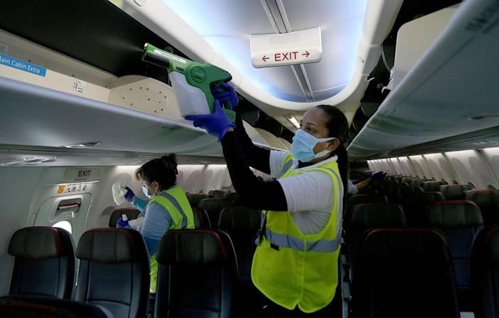 Wendy Valdez, an American Airlines employee, uses a electrostatic fogger during an on-board American Airlines aircraft cleaning process before departing from Miami International Airport, on Tuesday, June 30, 200. American Airlines hosted the media to highlight their new sanitizing methods as they boost passenger capacity on their flights amid a surge of new COVID-19 cases in Florida and across the country.