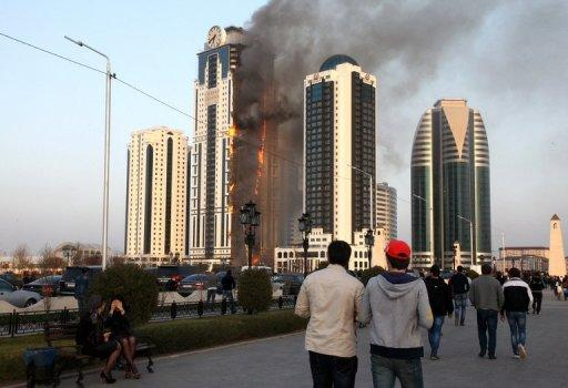Chechen people look at burning skyscraper in central Grozny on April 3, 2013