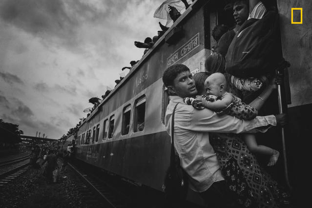 "<p>Photograph and caption by M.D. Tanveer Hassan Rohan/National Geographic Travel Photographer of the Year Contest. — ""This photograph was taken from Dhaka's airport rail station during the Eid vacation. People were returning to their village homes to spend Eid with families, and the rush at the last hour was immense. One man caught my attention: He was dangling on a train's handle with his family, trying to get inside the train. At that time, rain started and the train began to slowly move. The family had tickets to board the train, but couldn't get to their seats. There are many people like him, who come to Dhaka for work — leaving their families and home villages — so when they get vacation, they don't want to miss the opportunity to spend time with dear ones, no matter what."" Dhaka, Bangladesh. </p>"