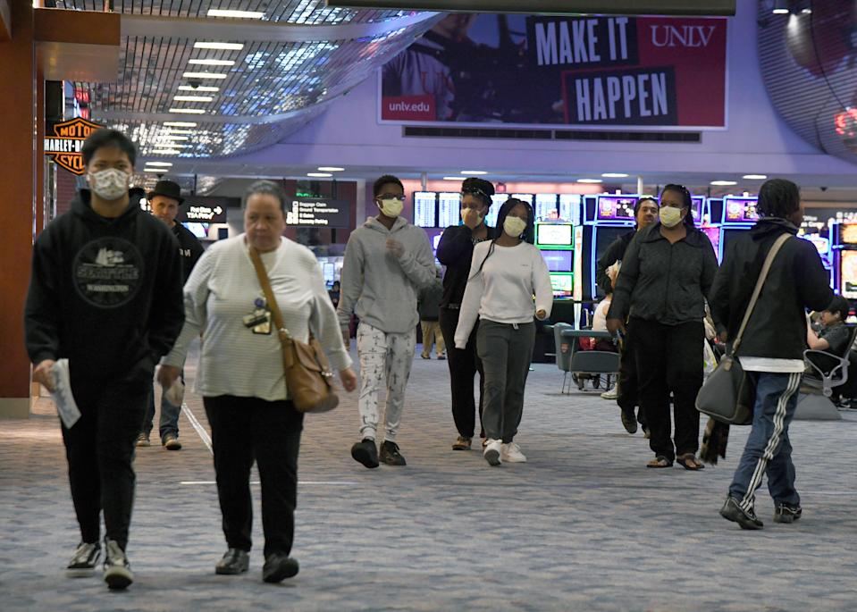 People, some wearing masks, walk through a concourse at McCarran International Airport as the coronavirus continues to spread across the United States on March 19, 2020 in Las Vegas, Nevada.