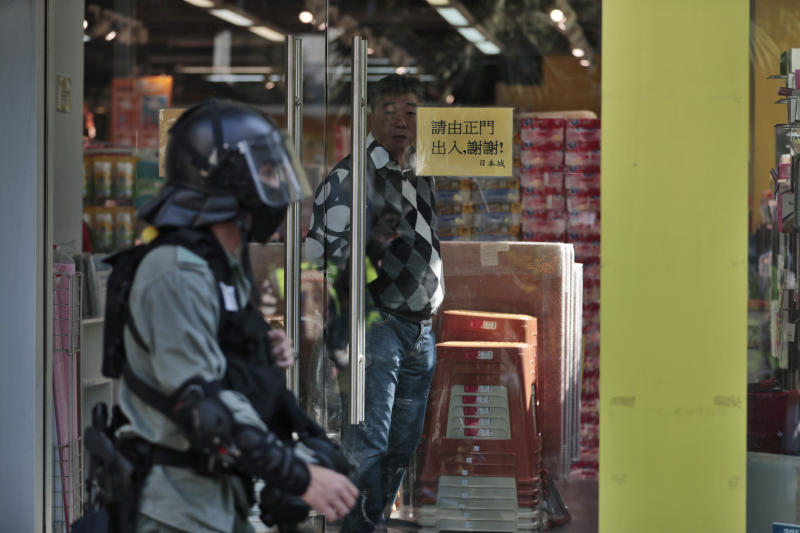 A man looks from inside a shop as a riot police officer patrols the area in anticipation of protests in Hong Kong, Sunday, Nov. 10, 2019. Authorities in Hong Kong have closed a subway station after protesters broke windows and damaged ticket machines. The semi-autonomous territory is in the sixth month of protests that began over a proposed China extradition law and have expanded to include demands for greater democracy and other grievances. (AP Photo/Dita Alangkara)