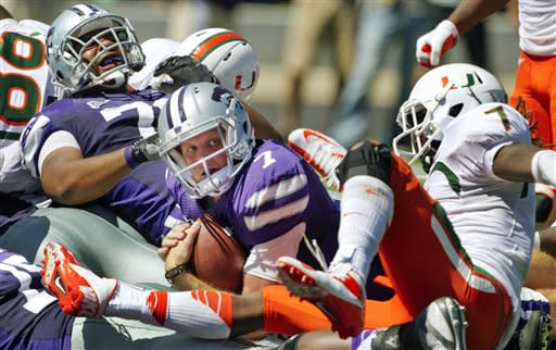 Kansas State quarterback Collin Klein (7) looks for an official's call after crossing the goal line past Miami defensive back Vaughn Telemaque (7) during the second half of an NCAA college football game in Manhattan, Kan., Saturday, Sept. 8, 2012. Kansas State offensive linesman Ethan Douglas (71) begins to celebrate on the play. (AP Photo/Orlin Wagner)