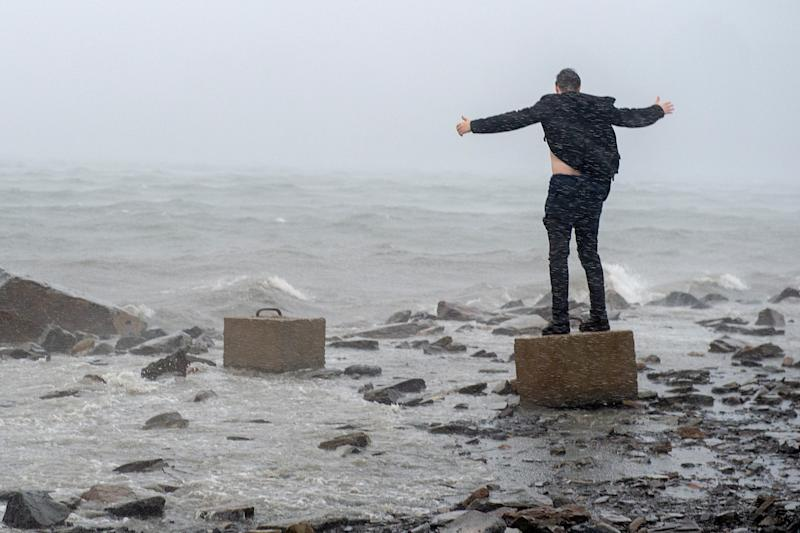 An unidentified man raises his arms in the winds from Hurricane Dorian along the Halifax harbor in Dartmouth, Nova Scotia, Canada, on Saturday, Sept. 7, 2019. (Andrew Vaughan/The Canadian Press via AP)