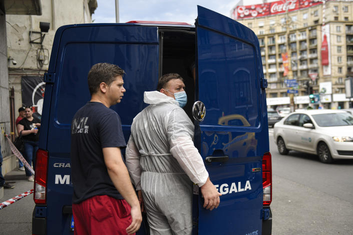 Forensic workers close the doors of a van after loading the body of Gholamreza Mansouri in Bucharest, Romania, Friday, June 19, 2020. Gholamreza Mansouri, a former judge from Iran sought by his country to face corruption charges has died after falling from a high floor inside a hotel. Romanian police said only that a man had fallen from a high floor at a hotel in Bucharest, the Romanian capital, and was found dead. (AP Photo/Andreea Alexandru)