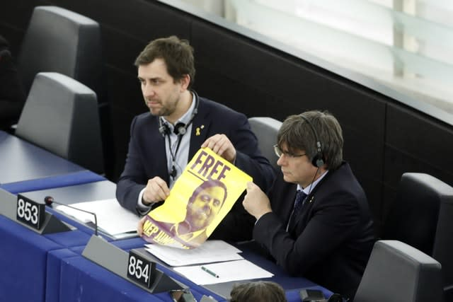 Catalan leader Carles Puigdemont, right, and former Catalan regional minister Antoni Comin, display a poster of jailed leader of the Catalonian ERC party Oriol Junqueras at the European Parliament in Strasbourg, eastern France