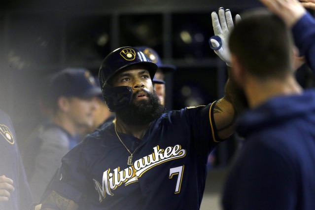 Milwaukee Brewers' Eric Thames is congratulated in the dugout after hitting a solo home run during the fourth inning of a baseball game against the Pittsburgh Pirates, Sunday, Sept. 22, 2019, in Milwaukee. (AP Photo/Aaron Gash)