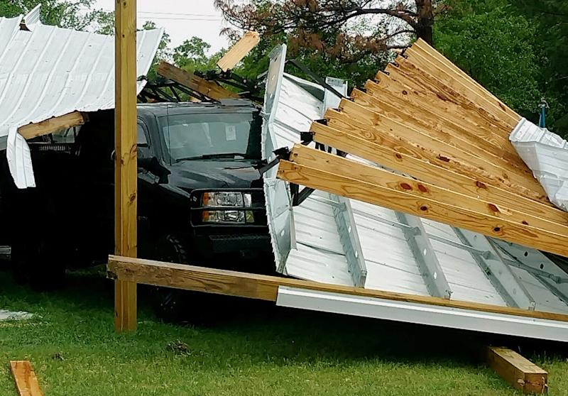 A damaged structure rests atop a pickup truck in the Screamer community of Henry County, Ala., after a suspected tornado touched down in the county Wednesday, April 5, 2017. National Weather Service meteorologist Mark Wool said a suspected tornado touched down Wednesday in Henry County, Alabama, before crossing into Georgia. (Michele W. Forehand/Dothan Eagle via AP)