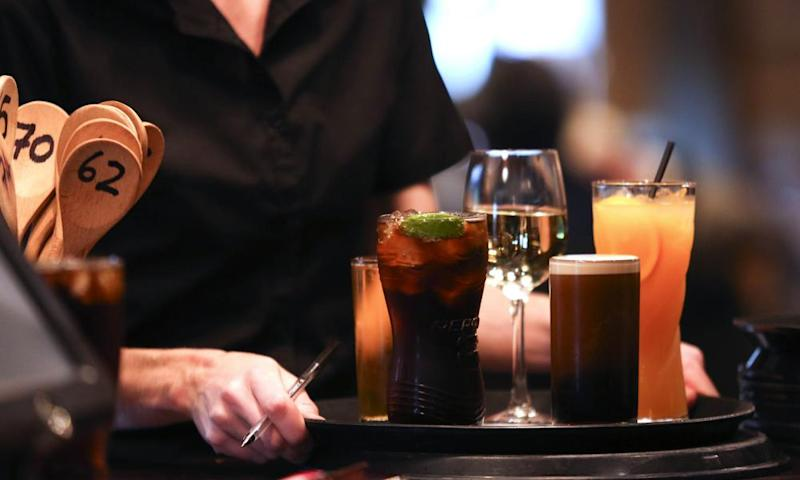 A female waiter carries a tray of drinks