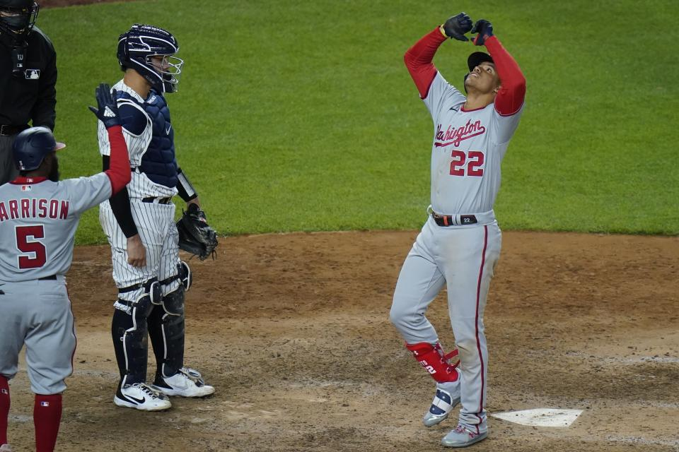 New York Yankees catcher Gary Sanchez, second from right, watches as Washington Nationals' Juan Soto (22) gestures as he reaches home plate after hitting a two-run home run of a baseball game Friday, May 7, 2021, in New York. (AP Photo/Frank Franklin II)