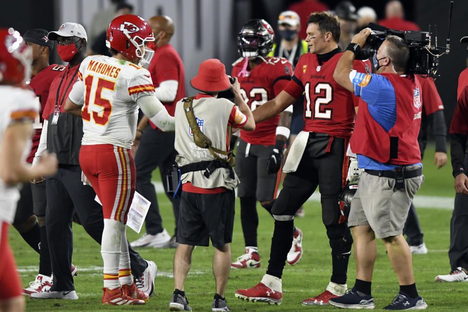 Tampa Bay Buccaneers quarterback Tom Brady reaches to shake the hand of Kansas City Chiefs quarterback Patrick Mahomes as other players, personnel and media linger after the game.
