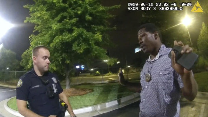 FILE- In this June 12, 2020 file photo from a screen grab taken from body camera video provided by the Atlanta Police Department Rayshard Brooks speaks with Officer Garrett Rolfe in the parking lot of a Wendy's restaurant, in Atlanta. Rolfe has been fired following the fatal shooting of Brooks and a second officer has been placed on administrative duty. The Fulton County District Attorney will announce charging decisions in the fatal shooting of Brooks during a news conference, Wednesday, June 17, 2020 in Atlanta. (Atlanta Police Department via AP, File)