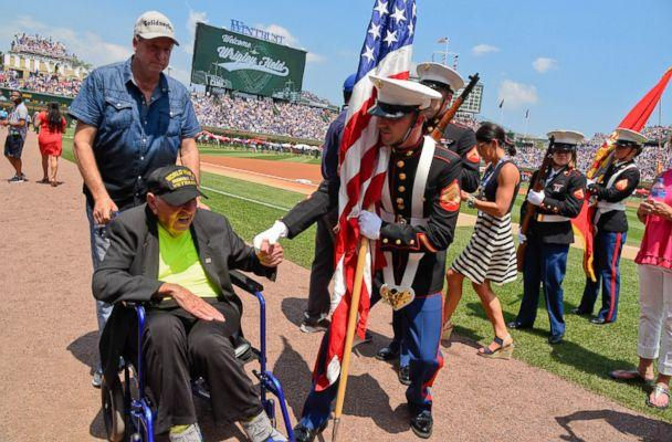PHOTO: World War II veteran Sidney Walton, left, is greeted by a member of the color guard before a baseball game between the Chicago Cubs and Detroit Tigers, July 4, 2018, in Chicago. (Matt Marton/AP)