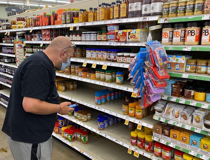 Instacart shopper Jeff Mitchell scans the shelves for the correct kind of peanut butter ordered by a customer inside a grocery store in Boulder County, Colorado. Instacart shopping is his full time job.