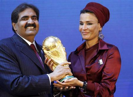Qatar's Emir Sheikh Hamad bin Khalifa al Thani and his wife Sheikha Moza Bint Nasser al-Misnad hold a copy of the World Cup trophy he received from FIFA President Sepp Blatter (unseen) after the announcement that Qatar will be the host nation for the FIFA World Cup 2022, in Zurich in this December 2, 2010 file photo.