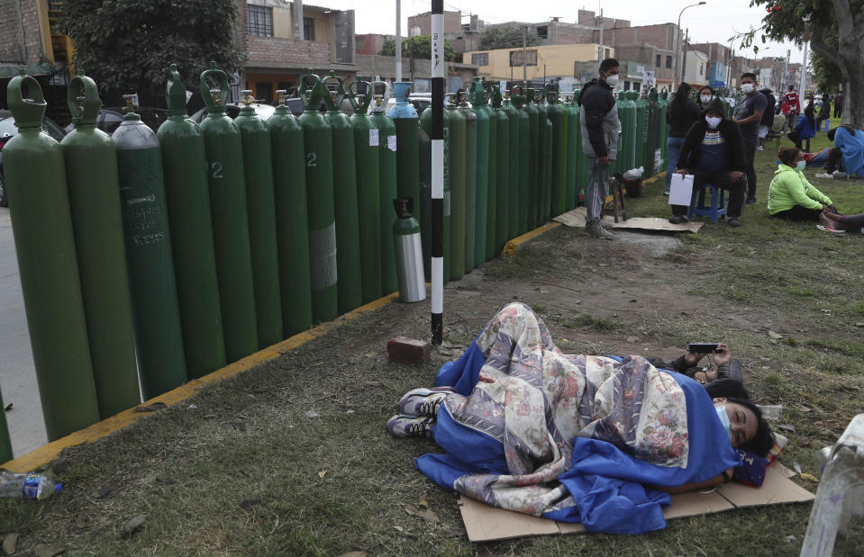 People lay next to their empty oxygen tanks as many wait for the refill shop to open in Callao, Peru, Monday, Jan. 25, 2021, amid the COVID-19 pandemic. A crisis over the supply of medical oxygen for coronavirus patients has struck nations in Africa and Latin America, where warnings went unheeded at the start of the pandemic and doctors say the shortage has led to unnecessary deaths. (AP Photo/Martin Mejia)
