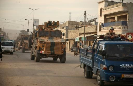 A Turkish military convoy headed for the south of Idlib province in northwest Syria passes through the town of Atareb