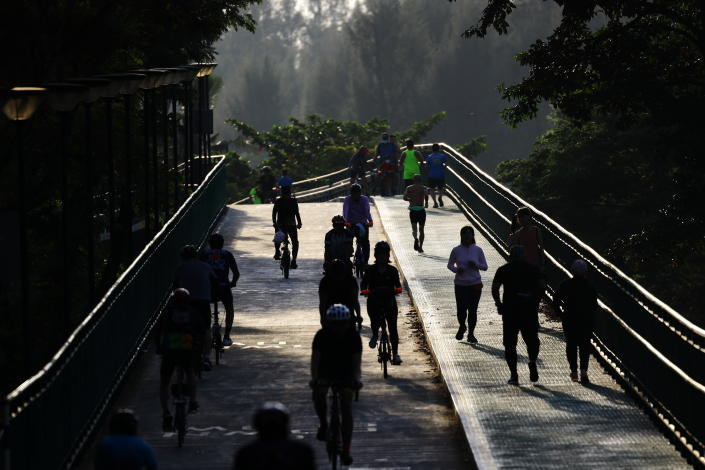People cycle and jog at a park on September 26, 2021 in Singapore.  (Photo by Suhaimi Abdullah/NurPhoto via Getty Images)