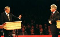 FILE PHOTO: President Clinton (R) leans on his podium as Republican presidential nominee Bob Dole gestures while..