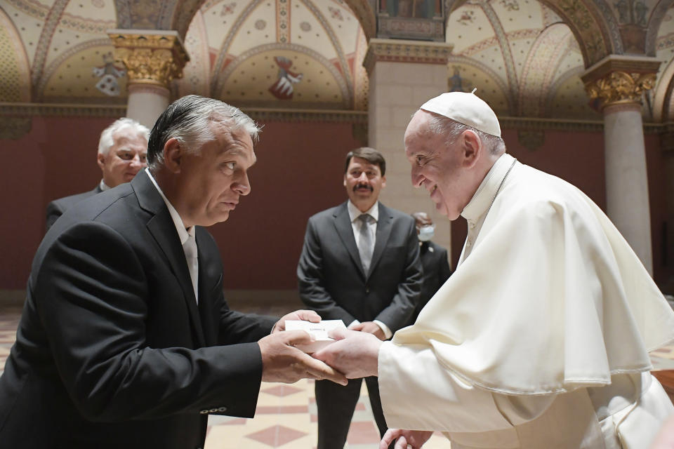 Pope Francis exchanges gifts with Hungarian Prime Minister Viktor Orban, at Budapest's Museum of Fine Arts, Sunday, Sept. 12, 2021. Francis is opening his first foreign trip since undergoing major intestinal surgery in July, embarking on an intense, four-day, two-nation trip to Hungary and Slovakia that he has admitted might be overdoing it. (Vatican Media via AP)