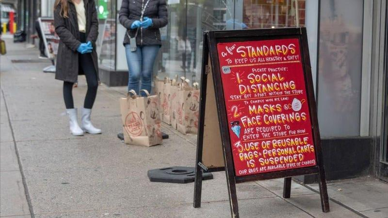 April 2020: a sandwich board lists Trader Joe's COVID protocols, including masks and distancing